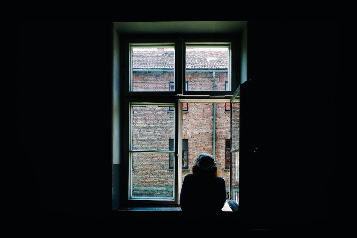Silhouette of a person looking out a window