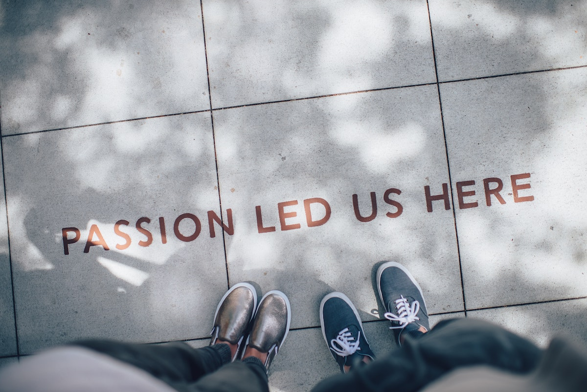 Passion led us here printed on pavement. Two people's feet are visible.