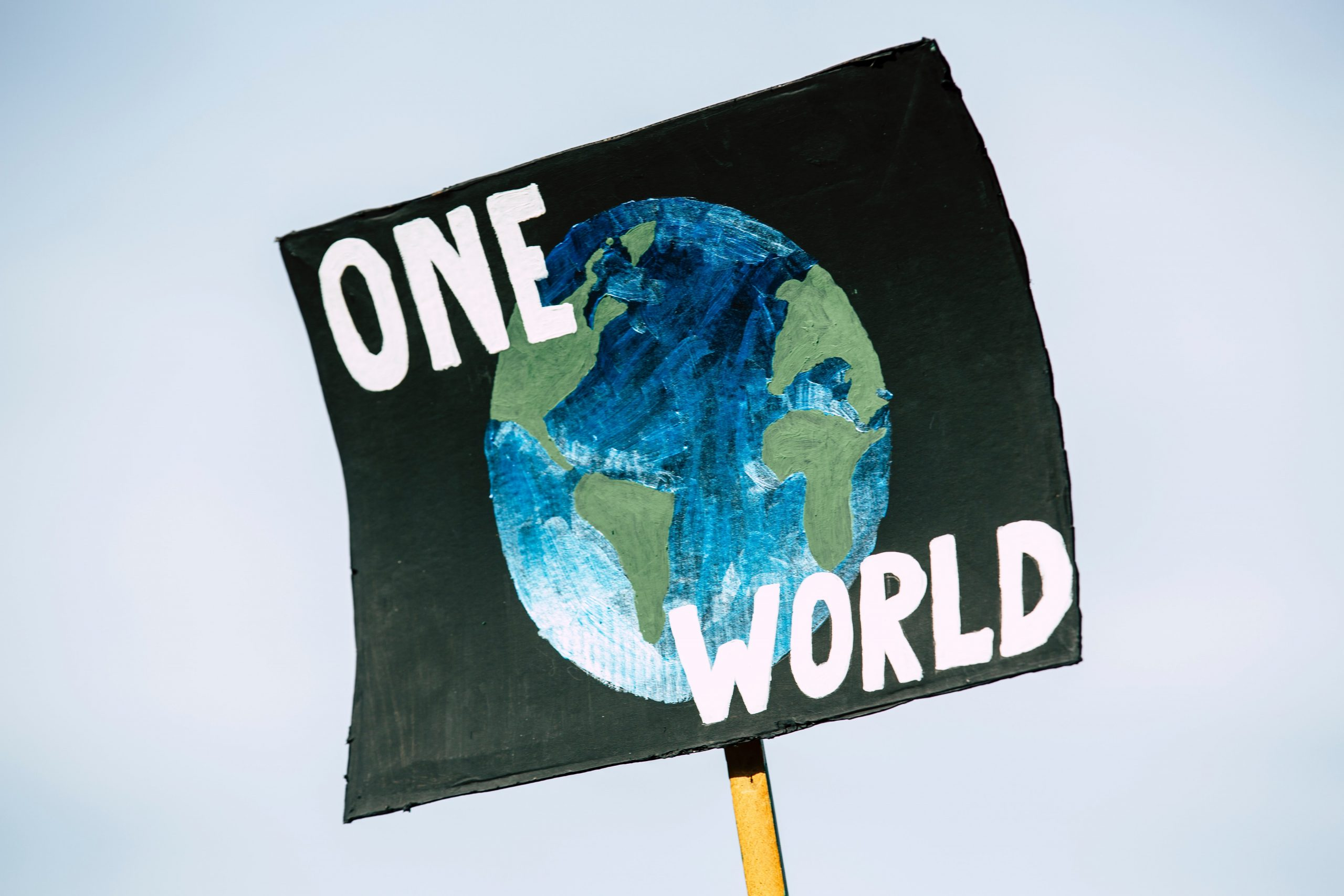 A protest sign in the air reads 'one world' in white text. The background is black and there is a blue and green drawing of the globe.